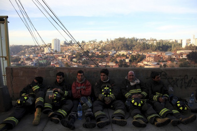 Firefighters take a break at the location where a forest fire burned several neighborhoods in the hills in Valparaiso. (REUTERS/Cristobal Saavedra)