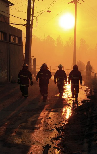 Firefighters walk past an area where a forest fire burned several neighborhoods in the hills in Valparaiso. (REUTERS/Carlos Gutierrez)