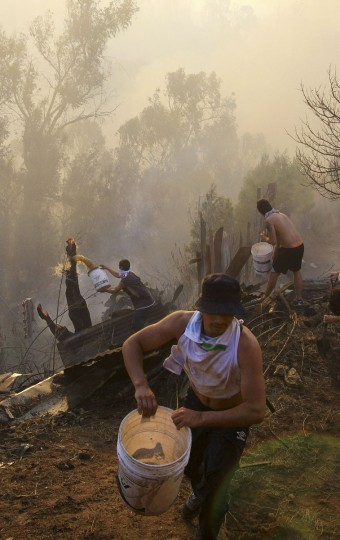 Residents work to put down a fire at the location where a forest fire burned several neighborhoods in the hills in Valparaiso. (REUTERS/Carlos Gutierrez)