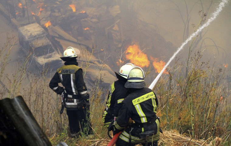 Firefighters work to put down a fire at the location where a forest fire burned several neighborhoods in the hills in Valparaiso. (REUTERS/Carlos Gutierrez)