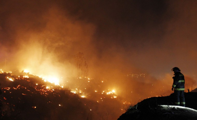 Firefighters work to put out a fire in Valparaiso. (REUTERS/Eliseo Fernandez)