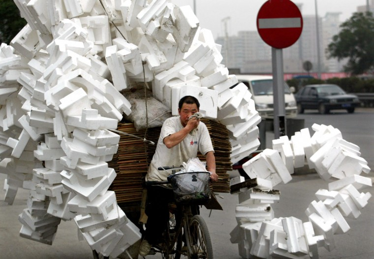 A Chinese man transfers recyclable rubbish which he collects from streets with a three-wheeled flat-bed bicycle in Beijing on June 28, 2002. (REUTERS/China Photo)