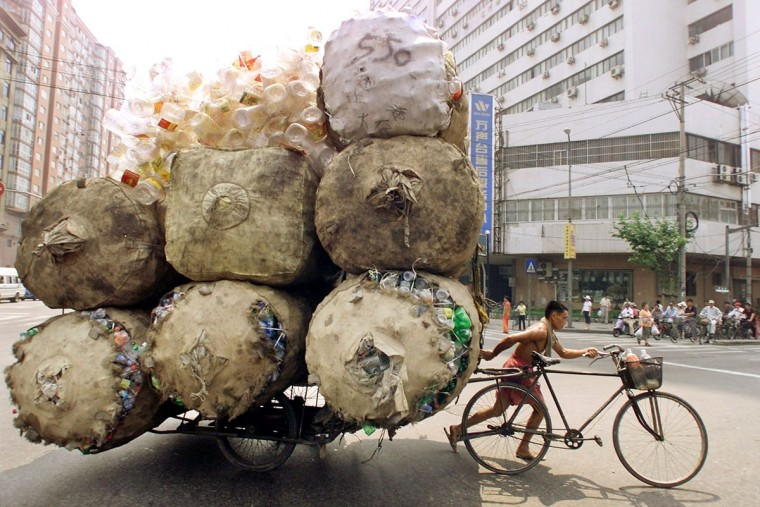 An enterprising Chinese man pulls a bicycle cart packed high with bags of recyclable plastic containers in Shanghai on July 25, 2002. (REUTERS/Claro Cortes IV)