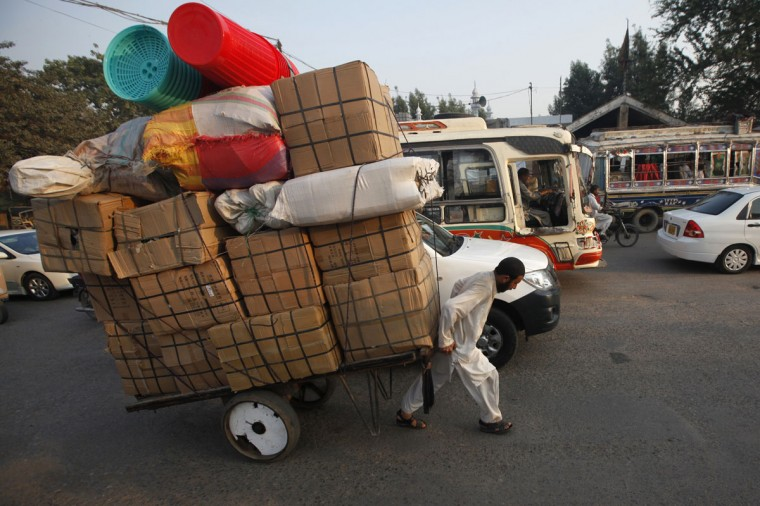 A laborer pulls a cart loaded with supplies while heading to a nearby market in Karachi, Pakistan on November 28, 2013. (REUTERS/Athar Hussain)