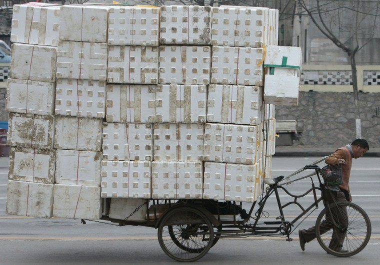A migrant worker pulls a cart loaded with discarded plastic foam for recycling in Nanjing, China on February 7, 2009. (REUTERS/Sean Yong)