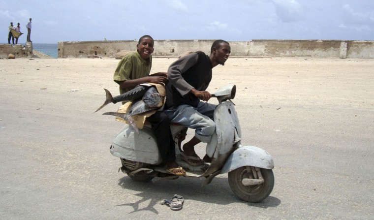 A Somali boy carries sword fish as he rides on a motorcycle taxi in southern Mogadishu, on August 16, 2010. (REUTERS/Feisal Omar)