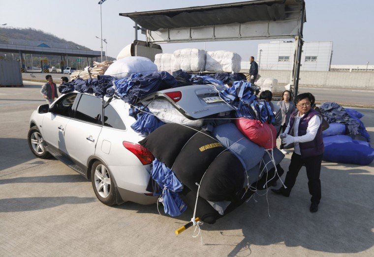 Workers of a South Korean company unload products made in inter-Korean Kaesong Industrial Complex in North Korea, to carry them into a truck after vehicles carrying the products arrived at the customs, immigration and quarantine (CIQ) office, just south of the demilitarized zone separating the North from South Korea in Paju. (REUTERS/Lee Jae-Won)
