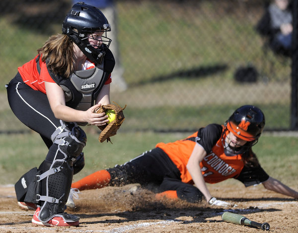 Dulaney catcher Maura McGinn, left, applies a late tag as McDonogh's Annie Britton crosses home plate during a softball game Tuesday, April 1. (Steve Ruark/BSMG)