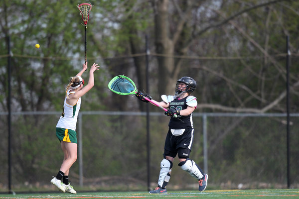 Wilde Lake's Kate Glaros, left, tries to block Atholton goalie Yasi Brewer's clear during the girls lacrosse game at Wilde Lake High School in Columbia Tuesday, April 22. (Jen Rynda/BSMG)
