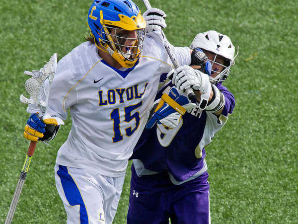 Loyola's Ryan Conrad is checked by Mt. St. Joe's Drew Harrison during the lacrosse matchup between Mount St. Joseph's and Loyola at the Loyola-Blakefield Campus in Towson on Tuesday, April 22. (Scott Serio/BSMG)