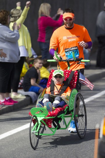 Craig Welton of Peabody pushes a companion in a wheelchair as they compete during the 2014 Boston Marathon. (David Butler II-USA TODAY Sports)