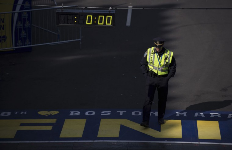 A Boston police officer walks across the finish line of the Boston Marathon in Boston. (REUTERS/Gretchen Ertl)