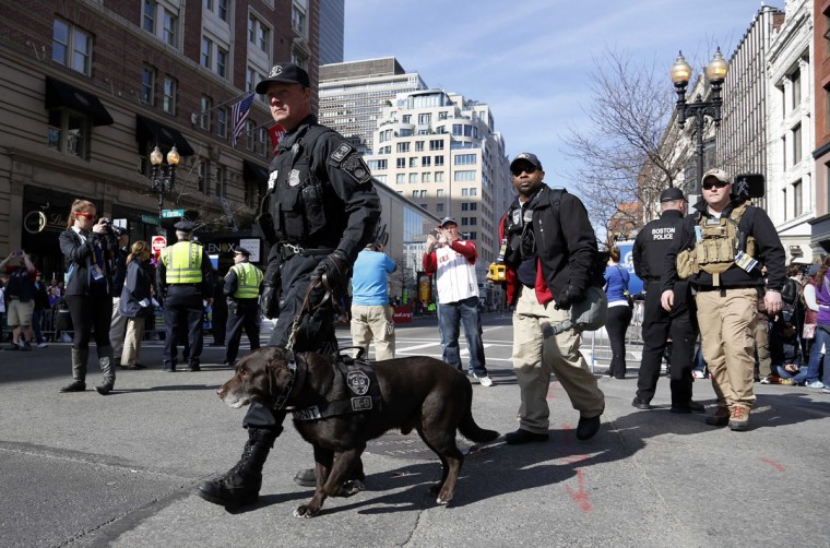 A Boston police officer from the K-9 unit patrols Boylston Street near the finish line before the start of the 2014 Boston Marathon. (Greg M. Cooper-USA TODAY Sports)