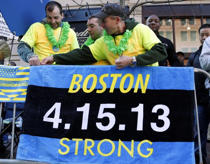 Andrew Lembcke (left) , Brandon Petrich (middle) and Bill Januszewski hang a Boston Strong banner before the start of the 2014 Boston Marathon. (Greg M. Cooper-USA TODAY Sports)