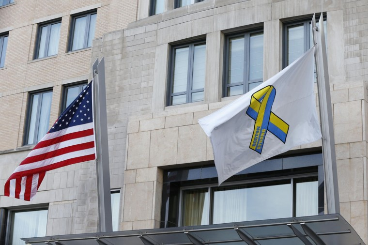 A Boston Strong flag and an American flag fly over Boylston Street before the start of the 2014 Boston Marathon. (Greg M. Cooper-USA TODAY Sports)