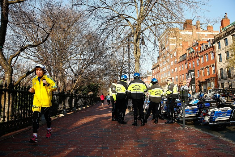 A runner warms up near a group of Boston Police officers prior to the start of the 2014 B.A.A. 5K on April 19, 2014 in Boston, Massachusetts. (Photo by Jared Wickerham/Getty Images)