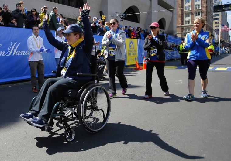 2013 Boston Marathon bombing survivor Erika Brannock (L) crosses the marathon finish line during a Tribute Run for survivors and first responders in Boston, Massachusetts April 19, 2014. The 118th running of the Boston Marathon will be held on April 21. (REUTERS/Brian Snyder)