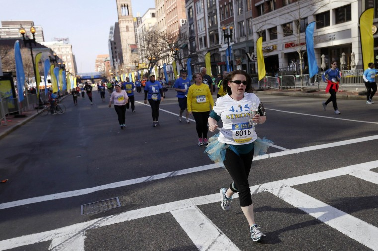 Shannon Silvestri, who was inured in last year's attacks on the Boston Marathon, runs in a tutu down Boylston Street in the Boston Athletic Association's 5K race in Boston, Massachusetts, April 19, 2014. (REUTERS/Dominick Reuter)