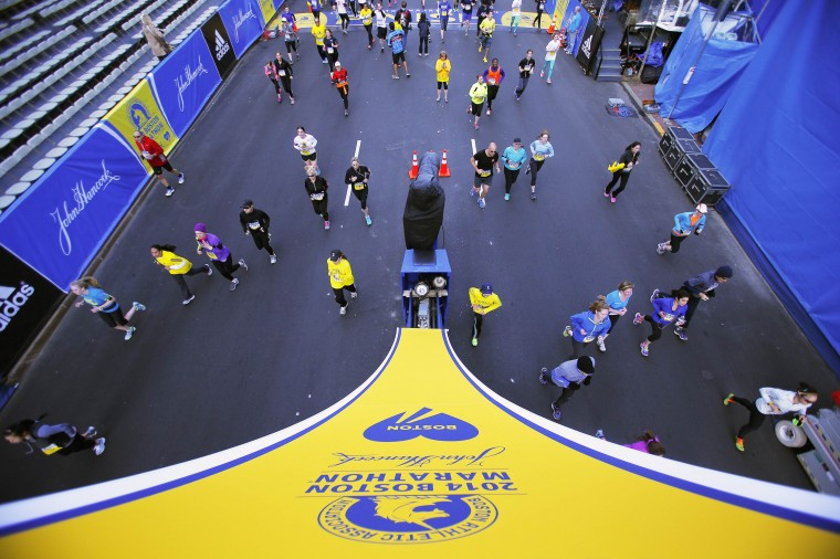 Runners cross over the Boston Marathon finish line while running the Boston Athletic Association's 5K race in Boston, Massachusetts April 19, 2014. The 118th running of the Boston Marathon will be held April 21. (REUTERS/Brian Snyder)