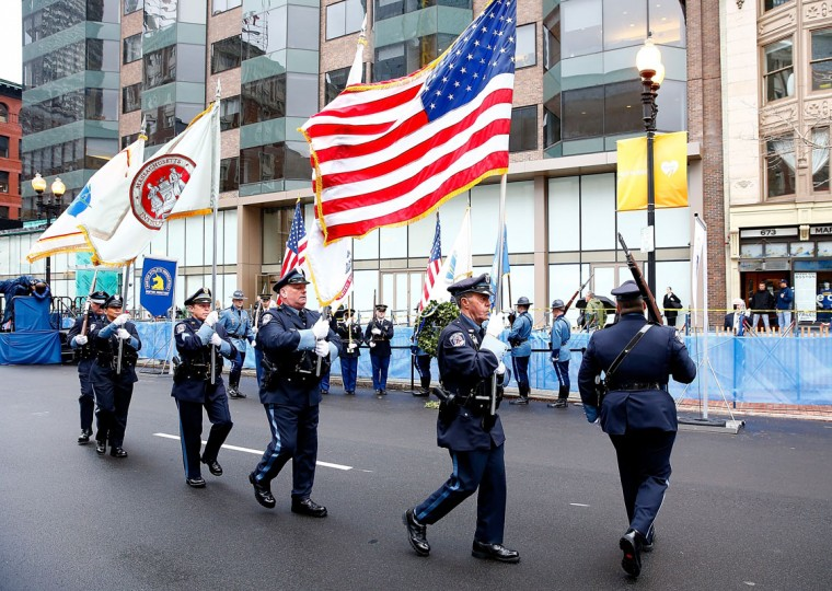Massachusetts state and local police and fire department members present flags during a wreath-laying ceremony commemorating the one-year anniversary of the Boston Marathon bombings on Boylston Street near the finish line on April 15, 2014 in Boston, Massachusetts. Last year, two pressure cooker bombs killed three and injured an estimated 264 others during the Boston marathon, on April 15, 2013. (Photo by Jared Wickerham/Getty Images)