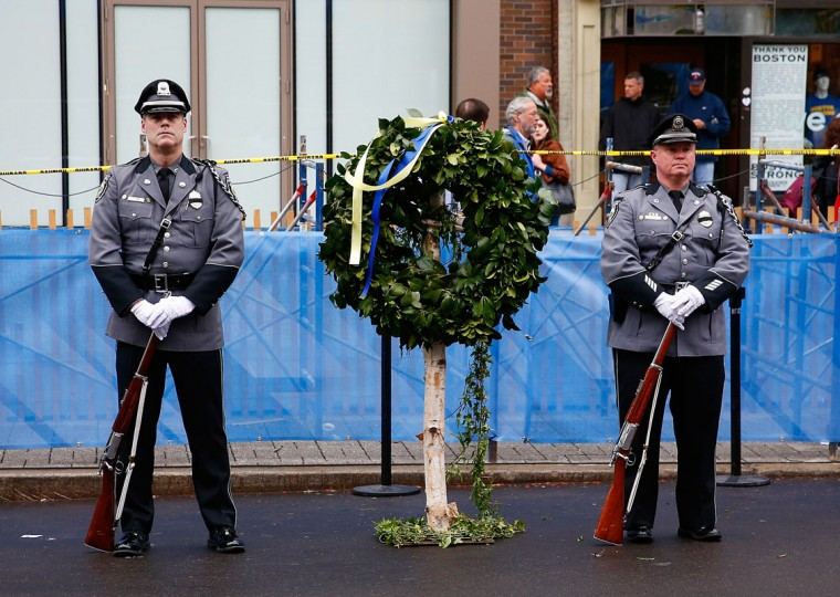 Massachusetts state and local police and fire department members stand near the site of one of the bombs following a wreath-laying ceremony commemorating the one-year anniversary of the Boston Marathon bombings on Boylston Street near the finish line on April 15, 2014 in Boston, Massachusetts. Last year, two pressure cooker bombs killed three and injured an estimated 264 others during the Boston marathon, on April 15, 2013. (Photo by Jared Wickerham/Getty Images)