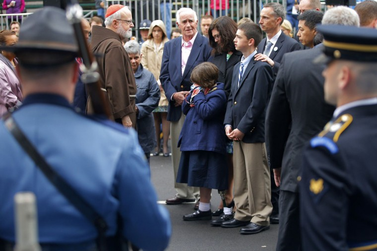 Boston Cardinal Sean O'Malley (L) joins the family of Boston Marathon bombing victim Martin Richard at the finish line for a wreath-laying ceremony in Boston, Massachusetts April 15, 2014. Martin Richard's sister Jane (5th R) wipes her face as she stands with her mother Denise (4th R), brother Henry (3rd R) and father Bill (2nd R). (Brian Snyder /Reuters)