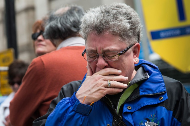 Sharon Neary, of Rochester, New York, cries while watching a billboard television screen broadcasting the ceremony commemorating the one year anniversary of the 2013 Boston Marathon Bombing , on April 15, 2014 in Boston, Massachusetts. Last year, two pressure cooker bombs killed three and injured an estimated 264 others during the Boston marathon, on April 15, 2013. Neary says she was standing near the site of the bombing before it went off. (Photo by Andrew Burton/Getty Images)