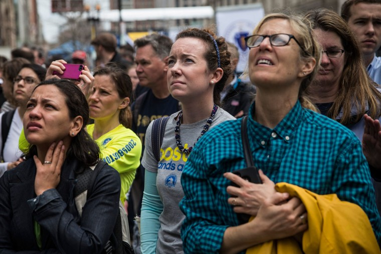 People watch a billboard television screen broadcasting the ceremony commemorating the one year anniversary of the 2013 Boston Marathon Bombing , on April 15, 2014 in Boston, Massachusetts. Last year, two pressure cooker bombs killed three and injured an estimated 264 others during the Boston marathon, on April 15, 2013. Neary says she was standing near the site of the bombing before it went off. (Photo by Andrew Burton/Getty Images)