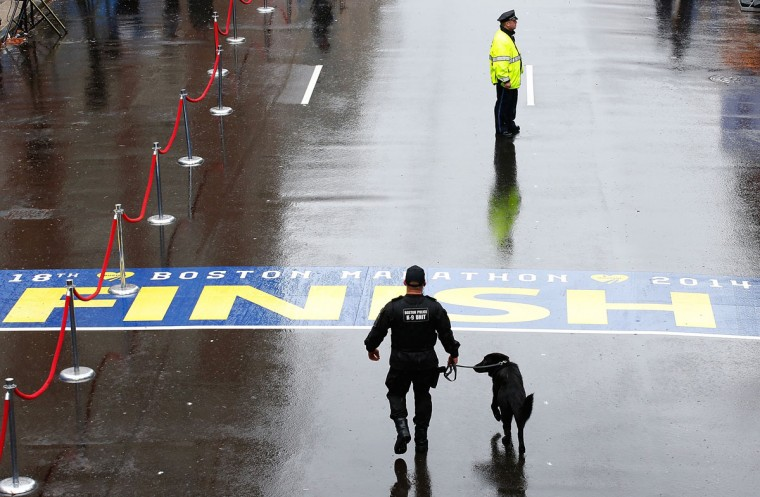 Boston Police officers and a K-9 unit patrol the finish line of the Boston Marathon prior to the flag raising ceremony commemorating the one-year anniversary of the Boston Marathon bombings on Boylston Street near the finish line on April 15, 2014 in Boston, Massachusetts. (Photo by Jared Wickerham/Getty Images)
