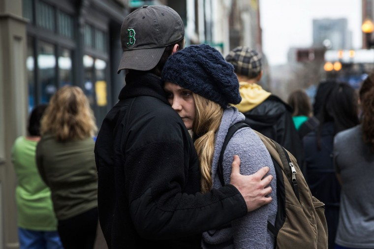 Tom Duggan hugs Sarah Rogo, who said they were both present last year at the marathon, while a billboard television screen broadcasts the ceremony commemorating the one year anniversary of the 2013 Boston Marathon Bombing , on April 15, 2014 in Boston, Massachusetts. Last year, two pressure cooker bombs killed three and injured an estimated 264 others during the Boston marathon, on April 15, 2013. Neary says she was standing near the site of the bombing before it went off. (Photo by Andrew Burton/Getty Images)