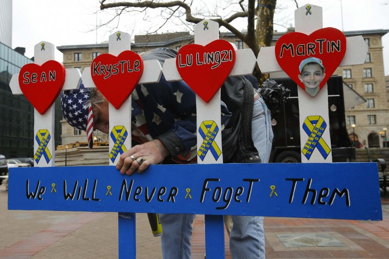 Kevin Brown puts up a hand made memorial for victims of the 2013 Boston Marathon bombings near the race's finish line in Boston, Massachusetts April 15, 2014, on the one year anniversary of the bombings. (Brian Snyder/Reuters)