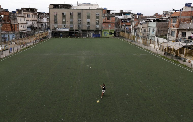 A boy plays soccer one day after the occupation of the Mare slums complex in Rio de Janeiro, March 31, 2014. The federal troops and police occupied the Mare slums complex on Sunday to help quell a surge in violent crime following attacks by drug traffickers on police posts in three slums on the north side of the city, government officials said. Less than three months before Rio welcomes tens of thousands of foreign soccer fans for the World Cup, the attacks cast new doubts on government efforts to expel gangs from slums using a strong police presence. The city will host the Olympics in 2016. (REUTERS/Ricardo Moraes)