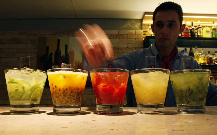 """A barman prepares """"Caipirinhas"""", Brazil's national cocktail, made with cachaca (sugar cane hard liquor), sugar and lemon or another fruit, at Fogo de Chao, a Brazilian steakhouse where food is prepared the traditional gaucho way, in Sao Paulo April 15, 2014. Sao Paulo is one of the host cities for the 2014 World Cup in Brazil. (REUTERS/Paulo Whitaker)"""