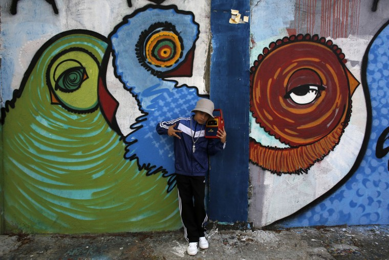 """A boy poses between graffiti-filled walls along """"Beco do Batman"""" (Batman's alley) in the Vila Madalena neighborhood, which is a well-known open-air graffiti museum, in Sao Paulo on April 20, 2014. Sao Paulo is one of the host cities for the 2014 World Cup soccer matches in Brazil. (REUTERS/Nacho Doce)"""