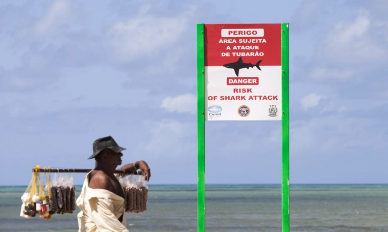 A street vendor walks near a sign warning of shark attacks at Boa Viagem beach in Recife on June 11, 2013. The Confederations Cup served as a dress rehearsal for the 2014 World Cup. (REUTERS/Helder Tavares)