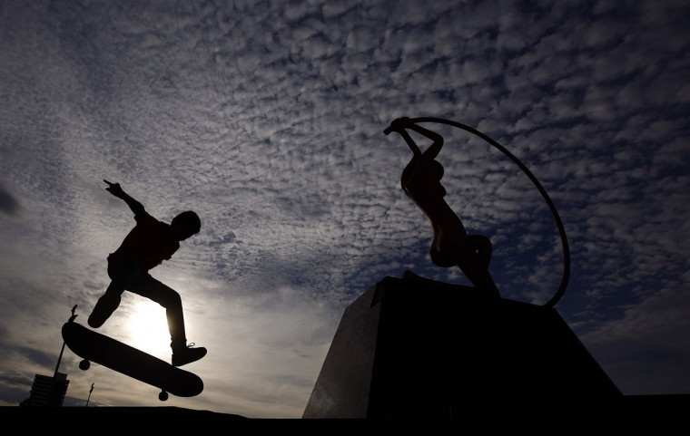 A young Brazilian boy practices his skateboarding skills near a sculpture at the beachfront of Fortaleza, on June 25, 2013. Fortaleza will be one of the 12 host cities of for the 2014 World Cup. (REUTERS/Kai Pfaffenbach)