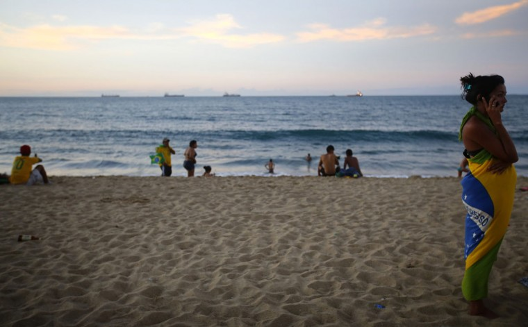 People are seen on the beach near a public viewing area while watching or listening to the Confederations Cup semifinal match between Brazil and Uruguay at the beachfront of Fortaleza, on June 26, 2013. Fortaleza will be one of the 12 host cities of the 2014 World Cup. (REUTERS/Kai Pfaffenbach)