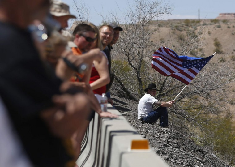 A protester waves the U.S. flag near others gathered on a bridge next to the Bureau of Land Management's base camp where seized cattle, that belonged to rancher Cliven Bundy, are being held at near Bunkerville, Nevada April 12, 2014. U.S. officials ended a stand-off with hundreds of armed protesters in the Nevada desert on Saturday, calling off the government's roundup of cattle it said were illegally grazing on federal land and giving about 300 animals back to rancher Bundy who owned them. (REUTERS/Jim Urquhart)
