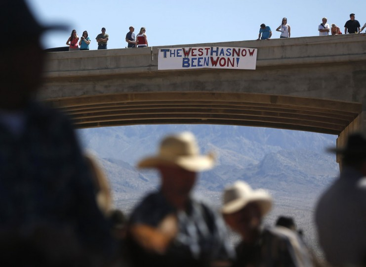 Protesters place a sign on a bridge near the Bureau of Land Management 's base camp where seized cattle, that belonged to rancher Cliven Bundy, are being held at near Bunkerville, Nevada April 12, 2014. U.S. officials ended a stand-off with hundreds of armed protesters in the Nevada desert on Saturday, calling off the government's roundup of cattle it said were illegally grazing on federal land and giving about 300 animals back to rancher Bundy who owned them. (REUTERS/Jim Urquhart)