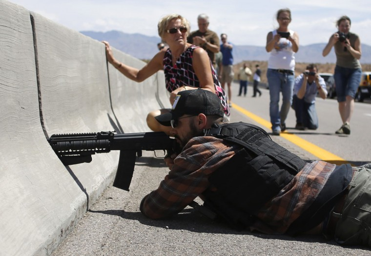 Protester Eric Parker from central Idaho aims his weapon from a bridge next to the Bureau of Land Management's base camp where seized cattle, that belonged to rancher Cliven Bundy, are being held at near Bunkerville, Nevada April 12, 2014. U.S. officials ended a stand-off with hundreds of armed protesters in the Nevada desert on Saturday, calling off the government's roundup of cattle it said were illegally grazing on federal land and giving about 300 animals back to rancher Bundy who owned them. (REUTERS/Jim Urquhart)