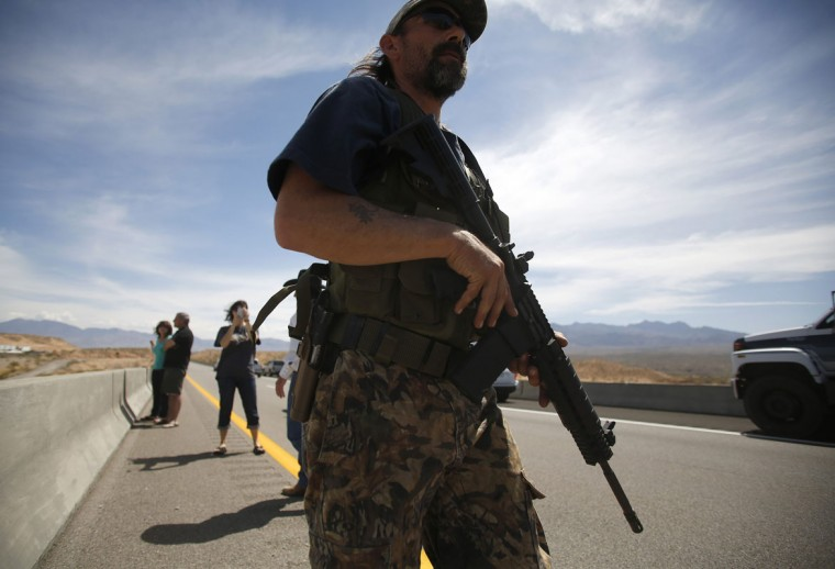 Protester Scott Drexler carries a rifle on a bridge next to the Bureau of Land Management's base camp where seized cattle, that belonged to rancher Cliven Bundy, are being held at near Bunkerville, Nevada April 12, 2014. U.S. officials ended a stand-off with hundreds of armed protesters in the Nevada desert on Saturday, calling off the government's roundup of cattle it said were illegally grazing on federal land and giving about 300 animals back to rancher Bundy who owned them. (REUTERS/Jim Urquhart)