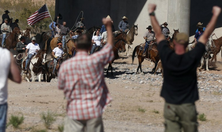 Protesters cheer on horseback riders as they herd cattle that belongs to rancher Cliven Bundy after they were released near Bunkerville, Nevada April 12, 2014. U.S. officials ended a stand-off with hundreds of armed protesters in the Nevada desert on Saturday, calling off the government's roundup of cattle it said were illegally grazing on federal land and giving about 300 animals back to rancher Bundy who owned them. (REUTERS/Jim Urquhart)