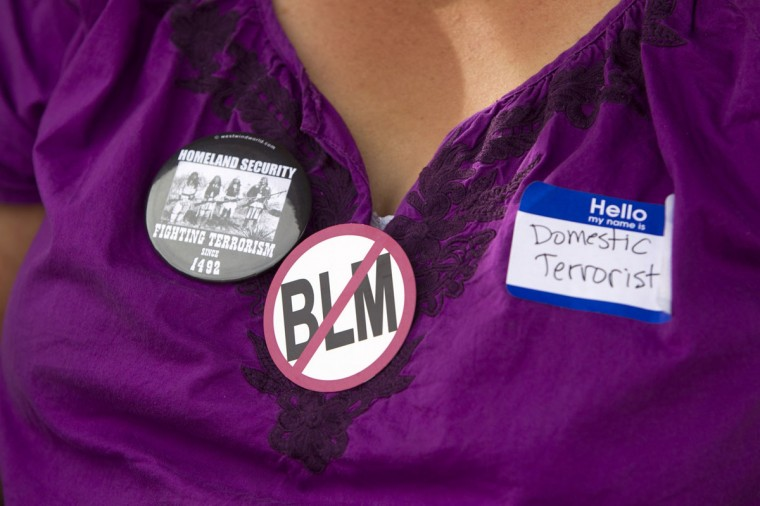 """A woman wears a """"No BLM"""" button during a Bundy family """"Patriot Party"""" near Bunkerville, Nevada, April 18, 2014. The family organized the party to thank people who supported rancher Cliven Bundy in his dispute with the Bureau of Land Management (BLM). The BLM last week called off an effort to round up Bundy's herd of cattle that it said were being illegally grazed in southern Nevada, citing concerns about safety. (REUTERS/Steve Marcus)"""