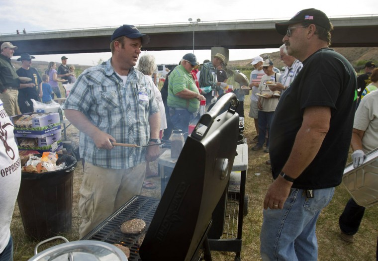 """Dave Bundy (L), a son of rancher Cliven Bundy, talks with Larry Skaggs of Overton, Nevada as he cooks hamburgers during a Bundy family """"Patriot Party"""" near Bunkerville, Nevada, April 18, 2014. The family organized the party to thank people who supported Cliven Bundy in his dispute with the Bureau of Land Management (BLM). The BLM last week called off an effort to round up Bundy's herd of cattle that it said were being illegally grazed in southern Nevada, citing concerns about safety. (REUTERS/Steve Marcus)"""