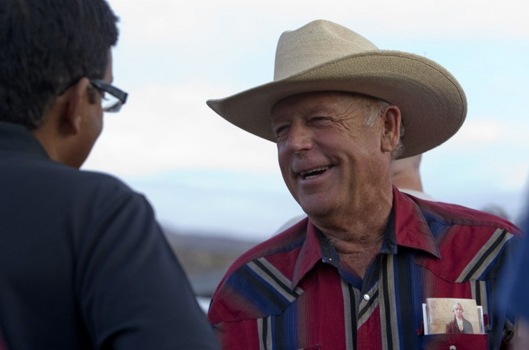 """Rancher Cliven Bundy (R) greets a supporter during a Bundy family """"Patriot Party"""" near Bunkerville, Nevada, April 18, 2014. The family organized the party to thank people who supported Bundy in his dispute with the Bureau of Land Management (BLM). The BLM last week called off an effort to round up Bundy's herd of cattle that it said were being illegally grazed in southern Nevada, citing concerns about safety. (REUTERS/Steve Marcus)"""