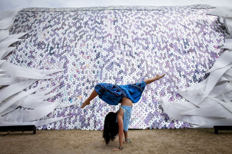 "Cynthia Kim, 22, performs dance moves in front of the ""Cryochrome,"" by artist James Peterson, on the first day of the second weekend of the Coachella Valley Music and Arts Festival at the Empire Polo Club in Indio, Calif., on Friday, April 18, 2014. (Jay L. Clendenin/Los Angeles Times/MCT)"