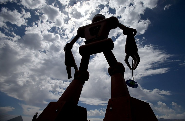 A man is dwarfed by a giant robot art sculpture on the Empire Polo Grounds on the first day of the Coachella Music and Arts Festival in Indio, Calif., on Friday, April 11, 2014. (Luis Sinco/Los Angeles Times/MCT)