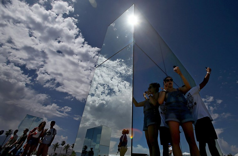 The sun reflects brightly on mirrored works of art as the gates open and participants take selfies on the the first day of the Coachella Music and Arts Festival in Indio, Calif., on Friday, April 11, 2014. (Luis Sinco/Los Angeles Times/MCT)