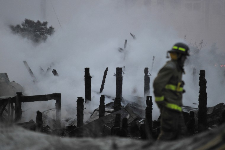 A firefighter walks near the remains of three beachfront homes which burned in Sea Isle City, N.J.. The houses were destroyed and numerous adjacent properties damaged, but there were no injuries reported, according to police on the scene. (Charles Mostoller/Reuters)