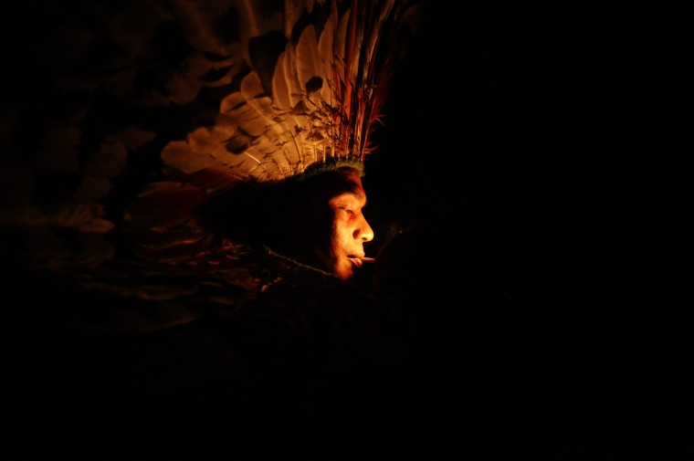 """A Huni Kui Indian smokes herbs during a ritual in the village of Novo Segredo along the Envira river of Brazil's northwestern Acre state. Many indigenous groups, including the Huni Kui, Ashaninka, and Madija, live in villages in the Brazilian rainforest near the border with Peru. Over the past three years, the Ashaninka and Madija say that they have seen more and more incursions on their territory from tribes, defined by Survival International as groups who have no peaceful contact with mainstream society. The """"Bravos,"""" or """"Braves,"""" carry out raids on other villages, putting the communities along the Envira River on permanent alert. (Lunae Parracho/Reuters)"""